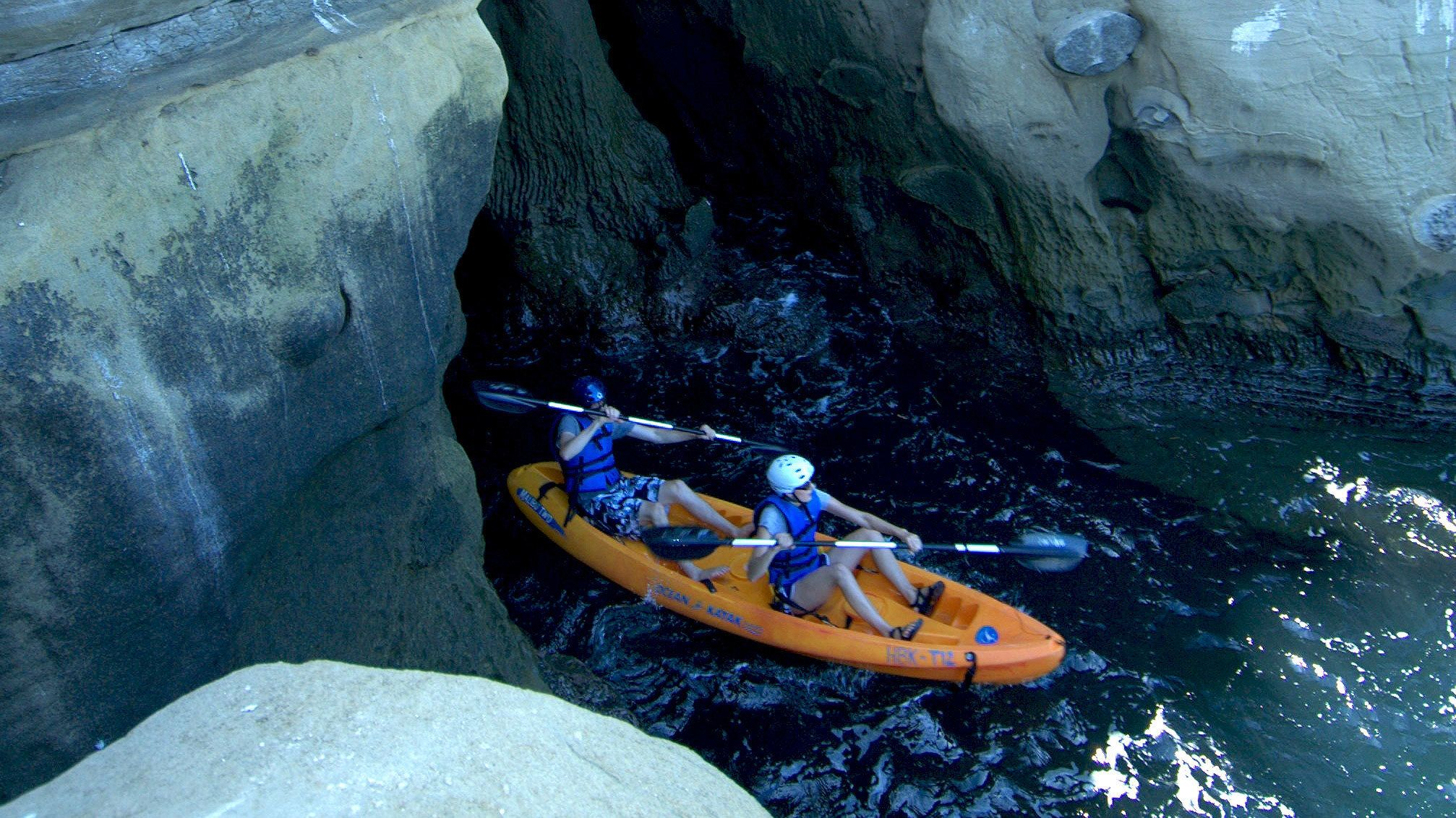 People coming out of La Jolla sea cave in kayak near San Diego