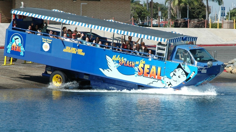 Show item 1 of 8. the hydra terra amphibious vehicle entering the water from the shore in San Diego