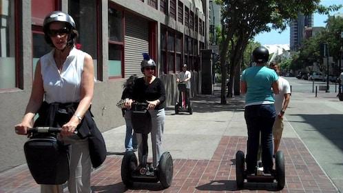 People in segways tutorial on street in San Diego