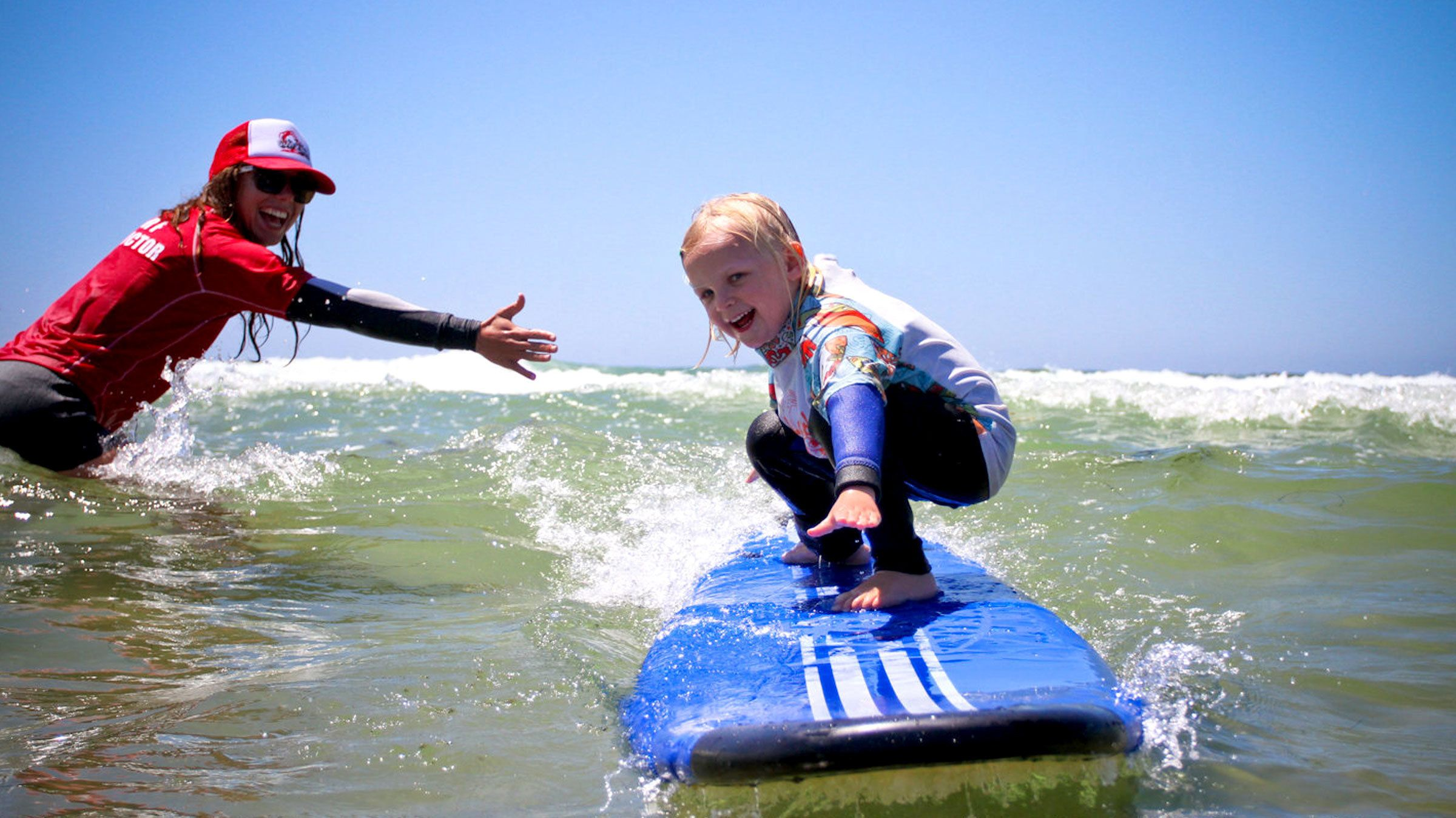 Little girl learning how to surf in San Diego