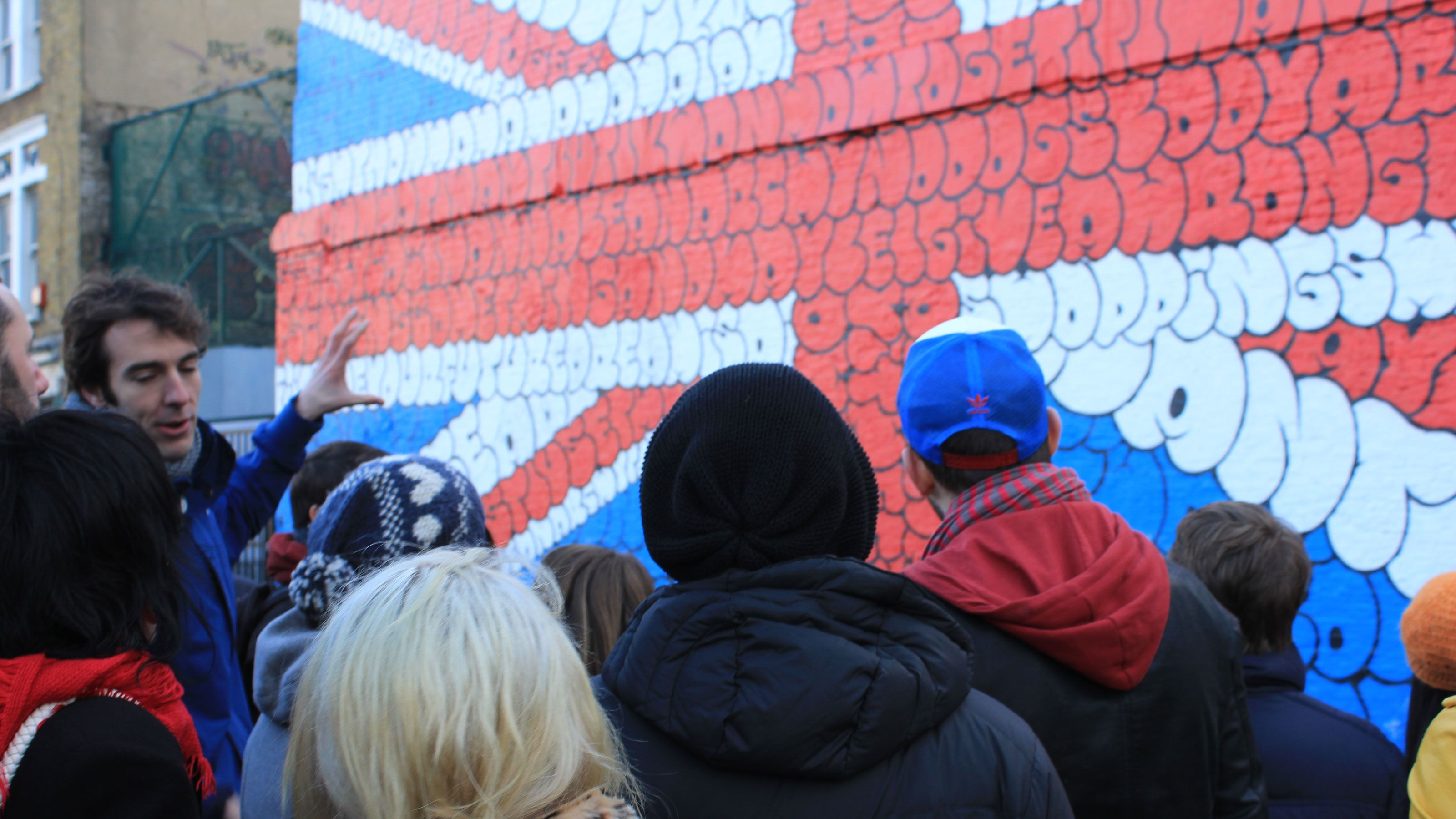people looking at street art paint on building in London