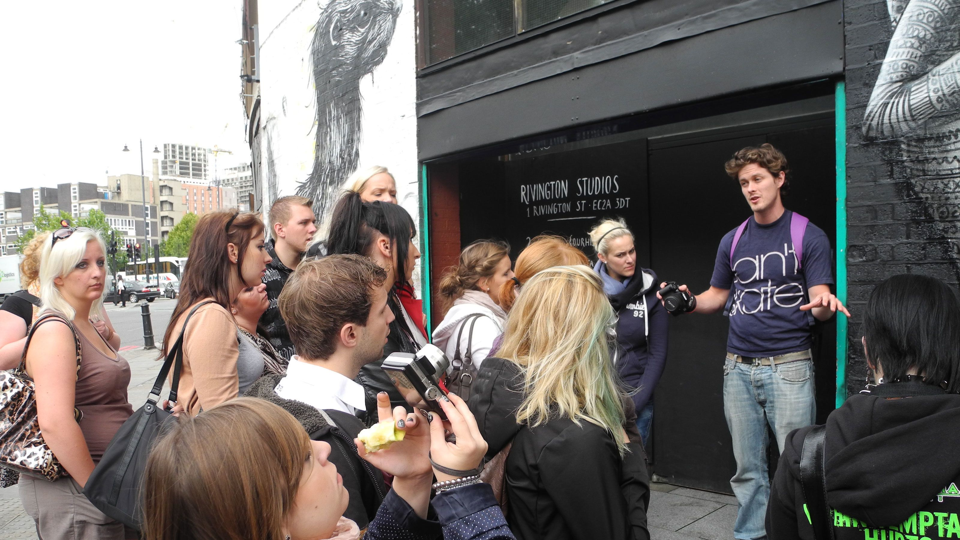 Tour guide with group on Street Art Tour of London