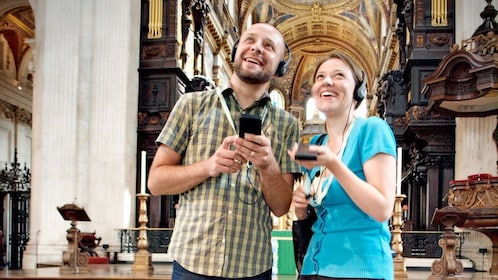 man and woman listen to audio tour inside St. Paul's Cathedral in London