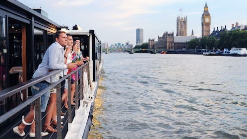 passengers enjoy sights of Parliament Building from river boat in London