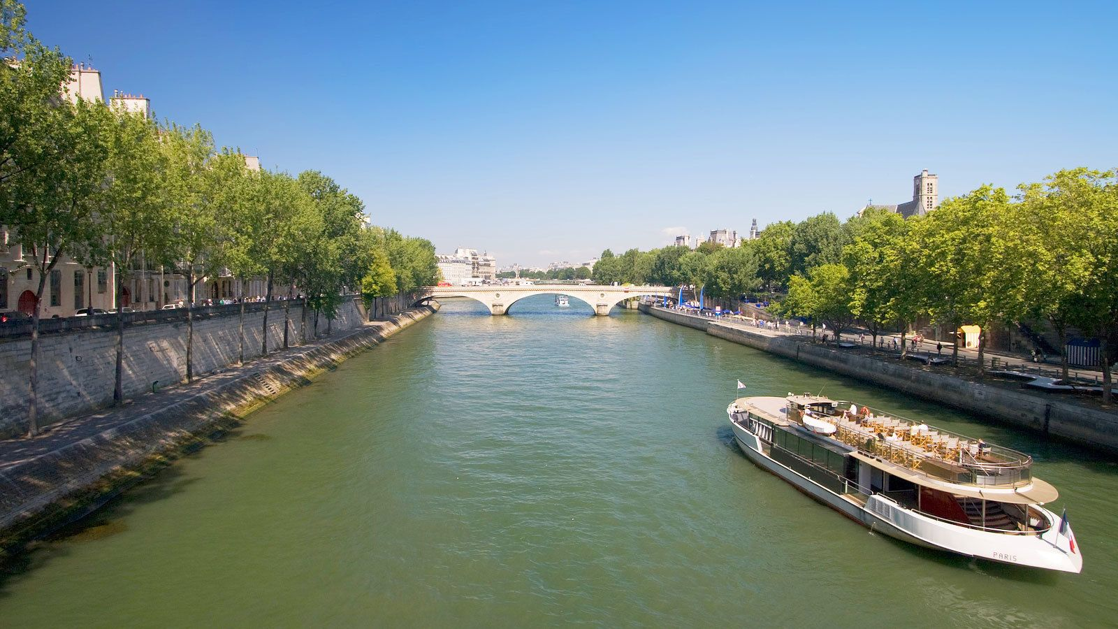 river ferry carrying passengers down channel in Paris