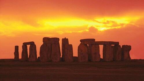 bright orange sunset behind Stonehenge in London