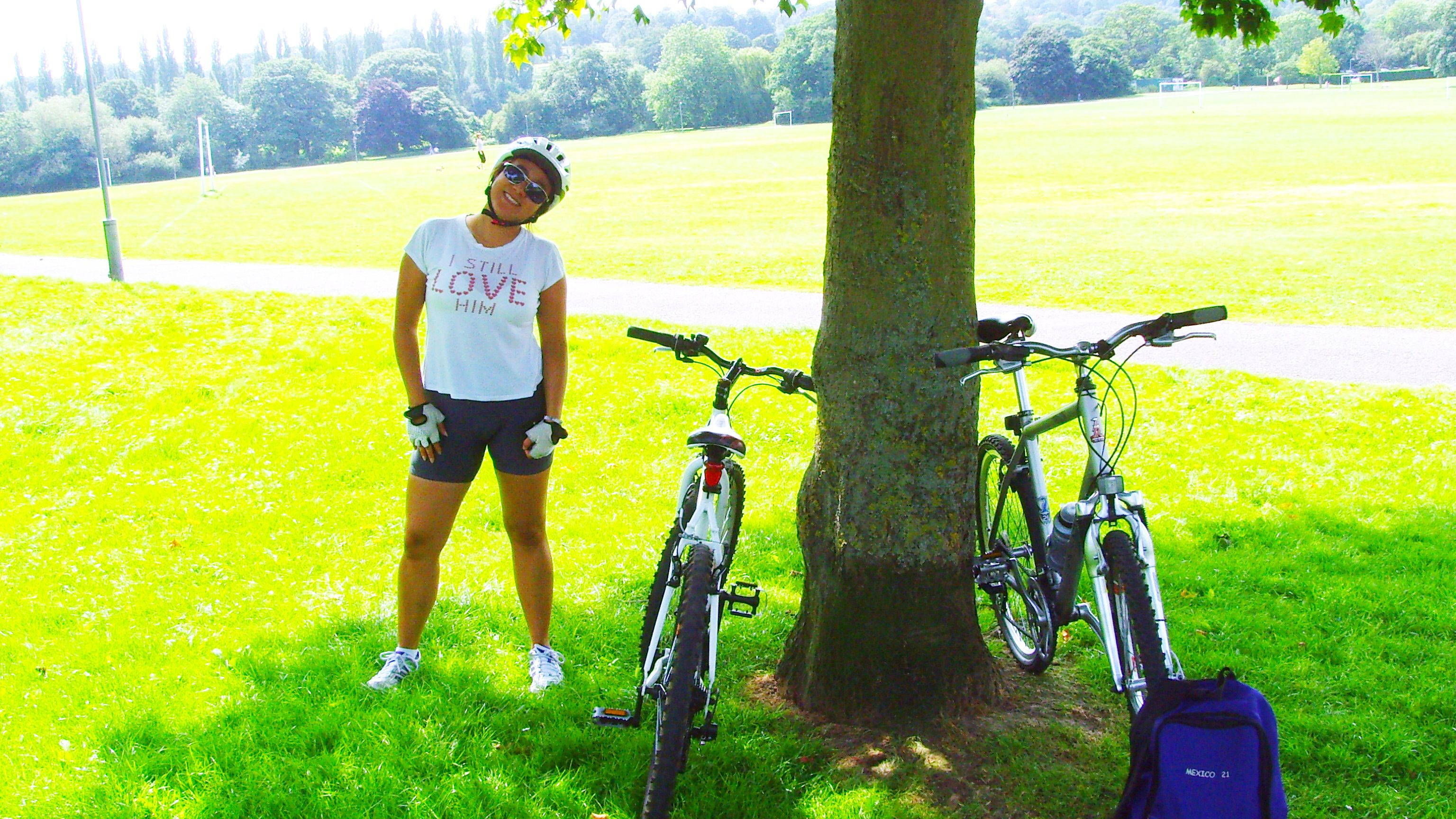 woman stands under tree next to her bicycle in London