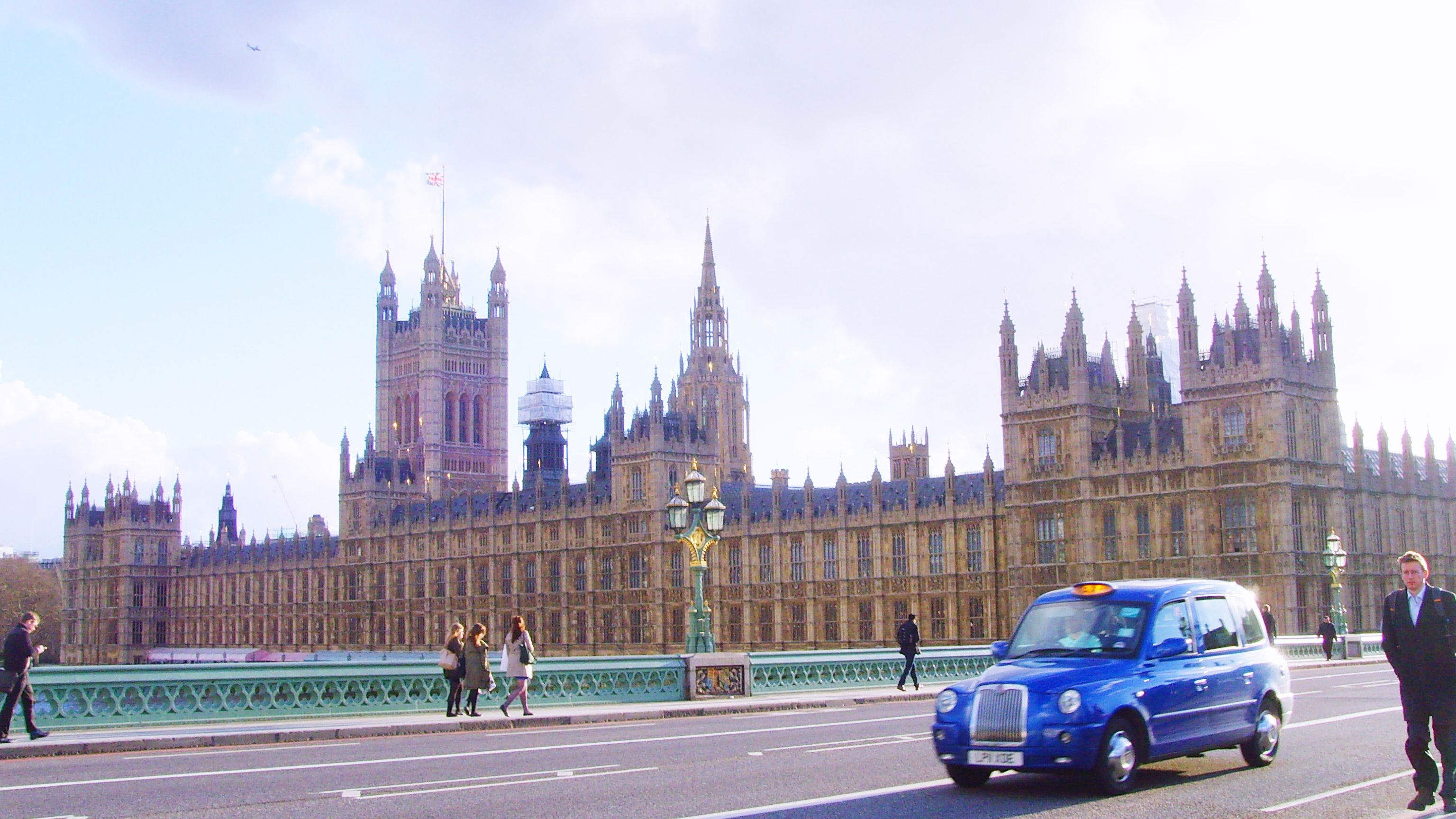 blue taxi driving past House of Parliament in London