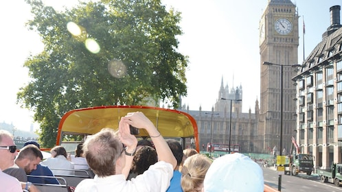 tourist in open air bus take photos of Big Ben in London