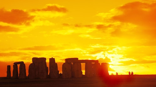 bright yellow sunset behind Stonehenge in London