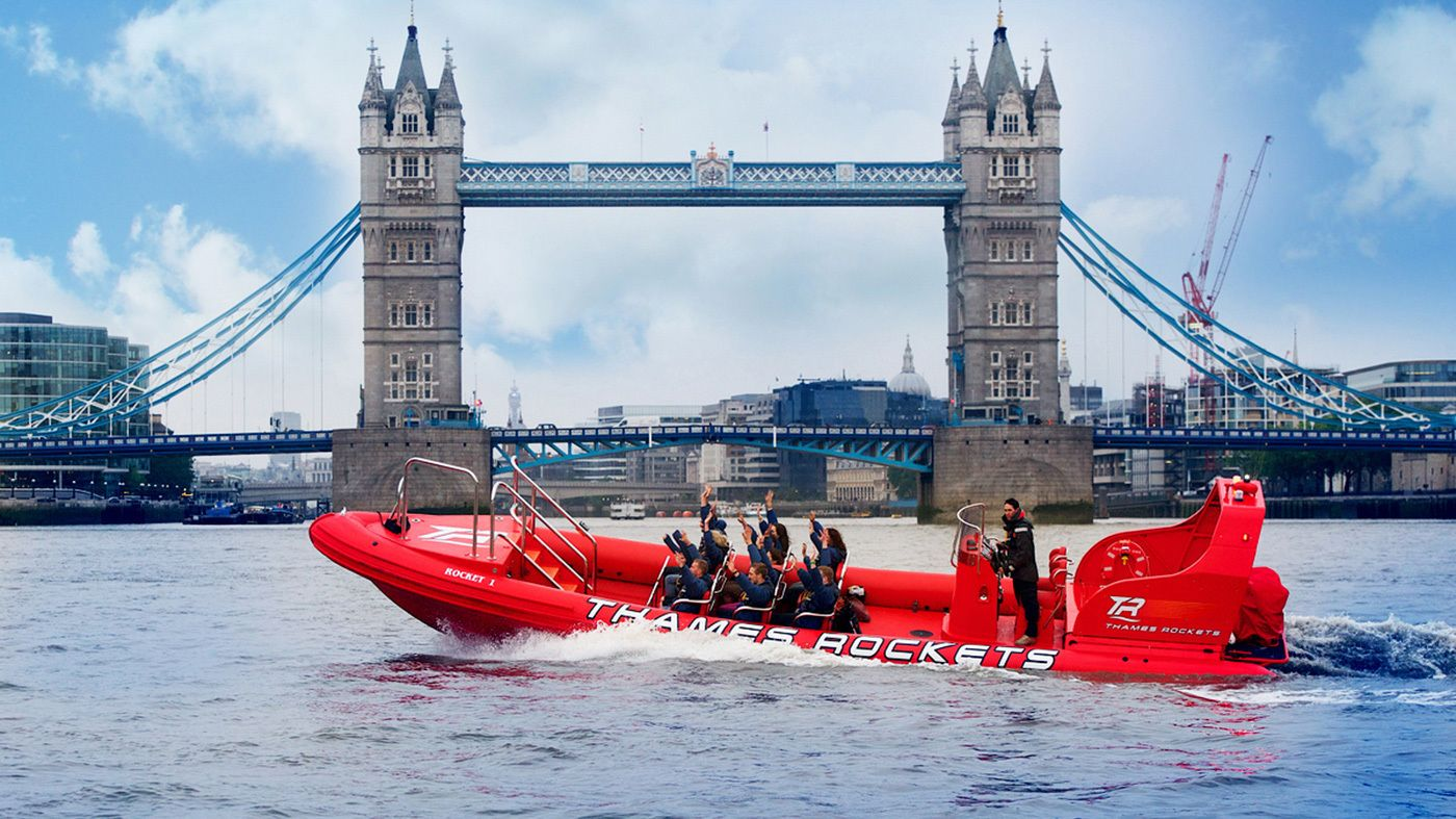 Speedboat with passengers speed in harbor near London Bridge
