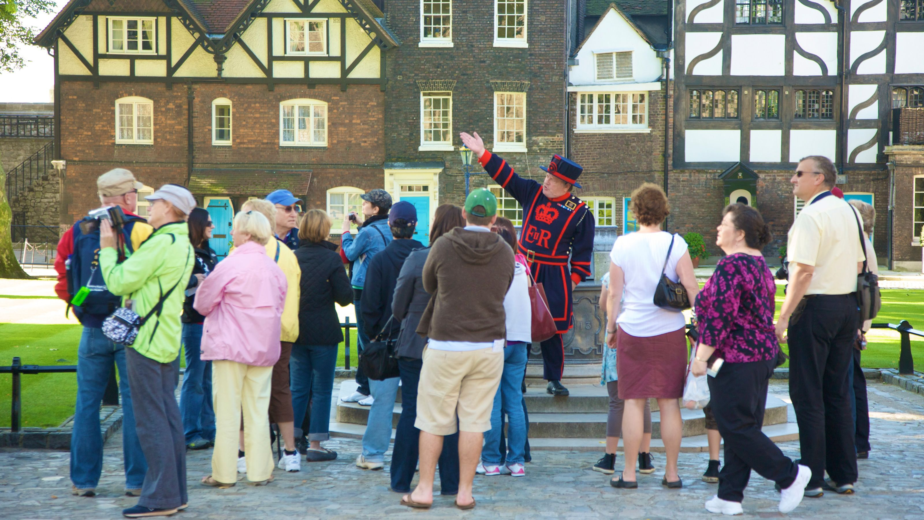 beefeater tour guide directs visitors attention to the left at Tower of London