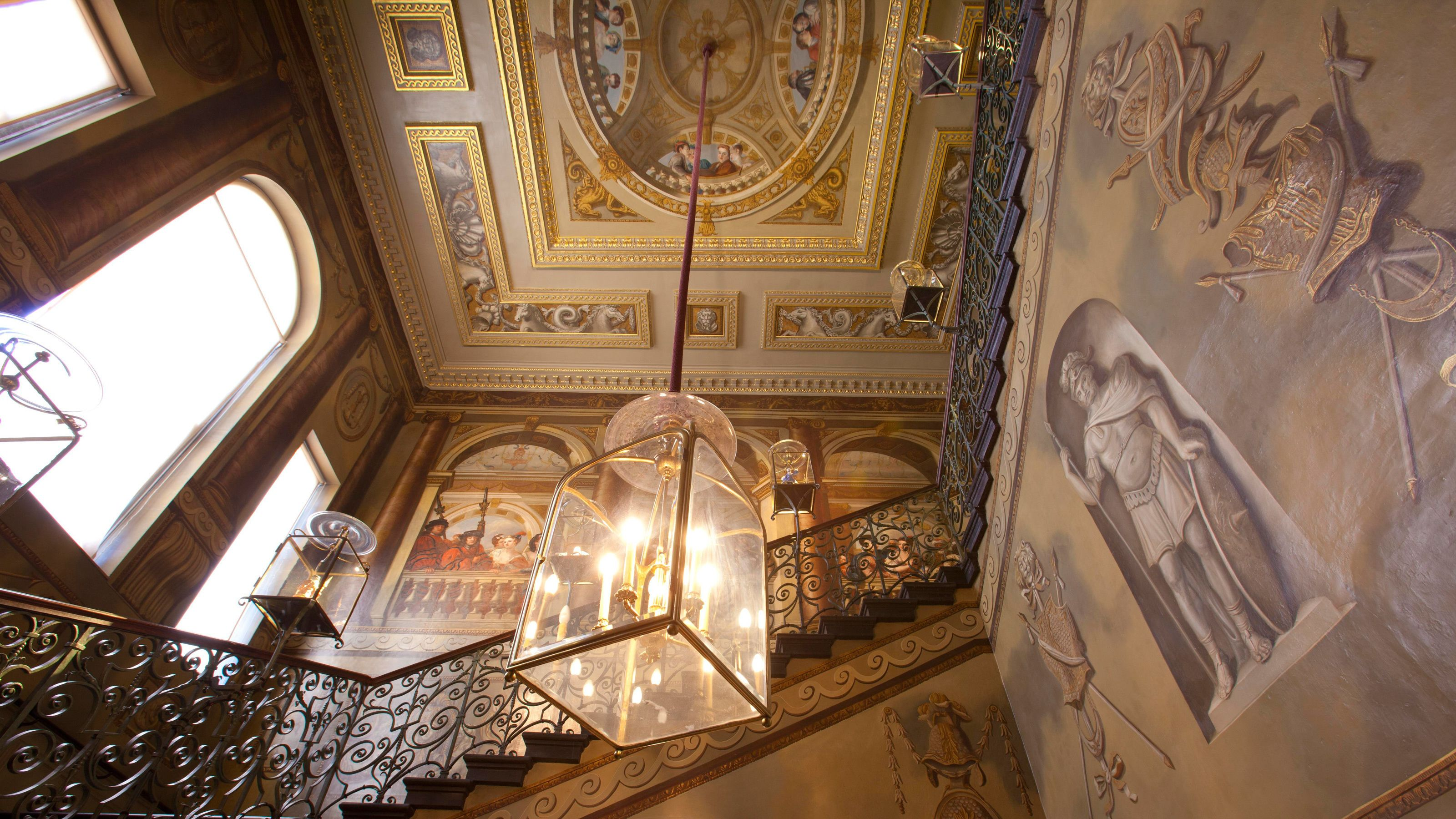intricate artwork within staircase and lamps in Kensington Palace in London