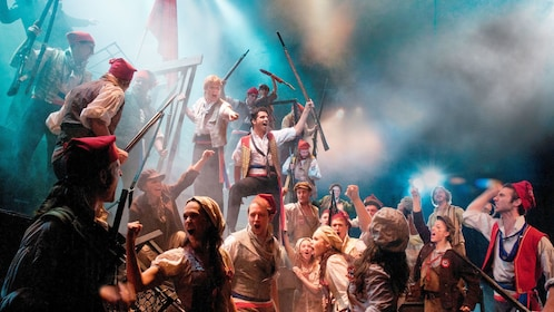 many men and woman in costume singing in play of Les Misérables in London