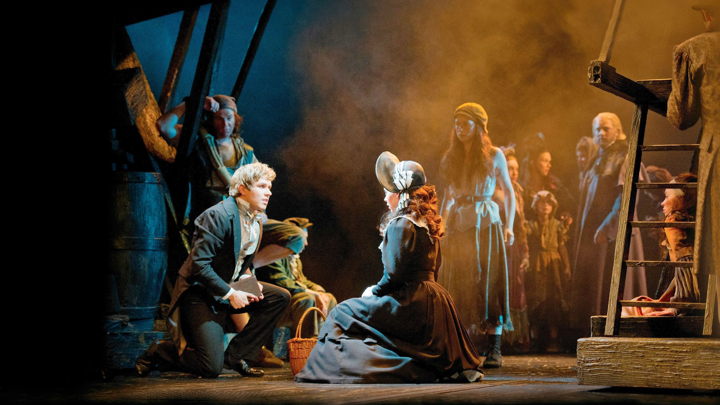 man kneels before woman in theatre stage play of Les Misérables in London