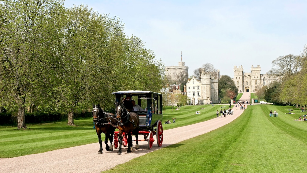 Show item 10 of 10. horse drawn carriage walks down road from Windsor Castle in London