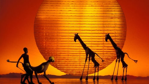 actors dressed as giraffes and lion in stage play of Lion King in London