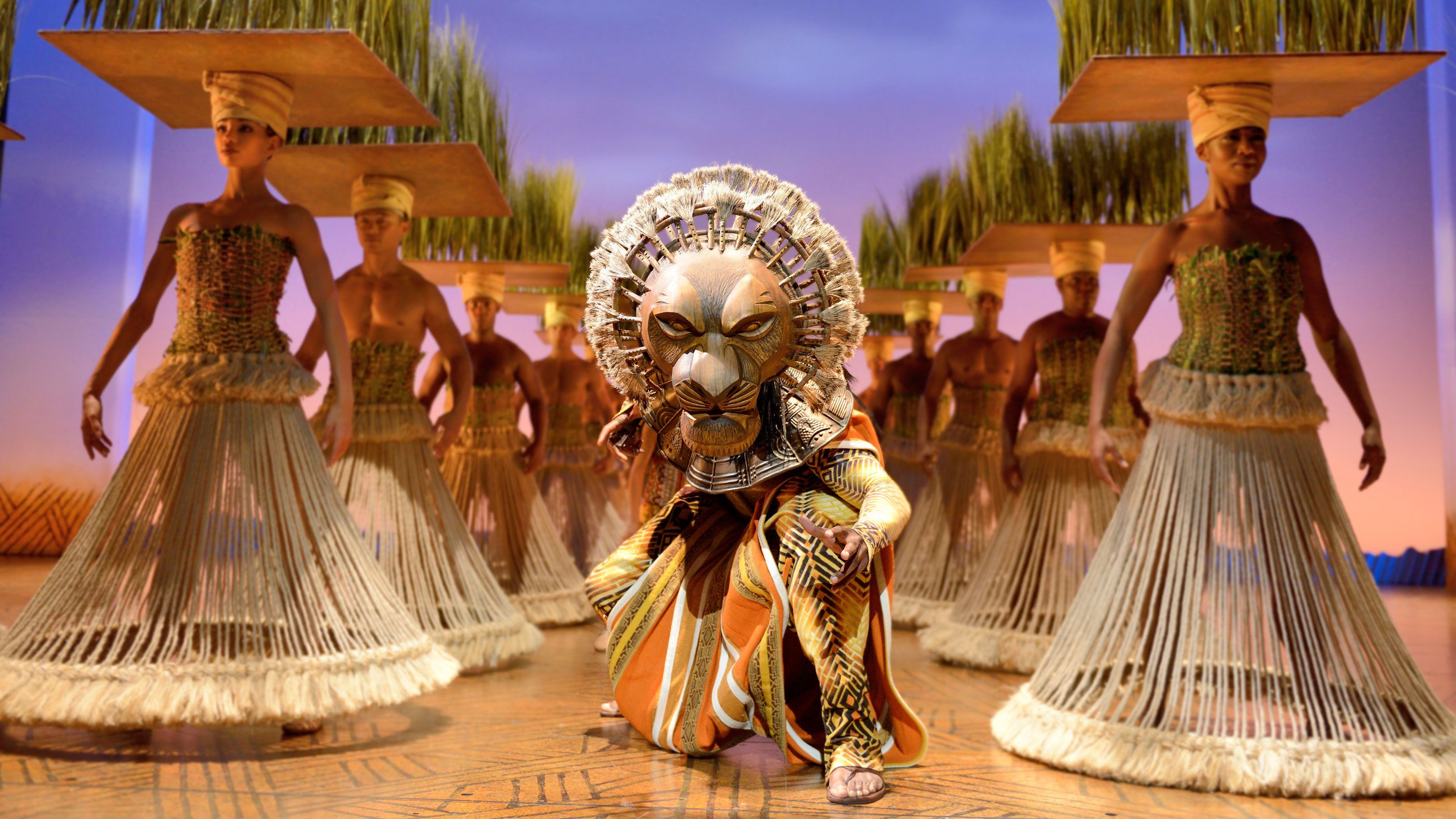 Actor portraying Lion crouches between two lines of other actors in theatre play of Lion King in London