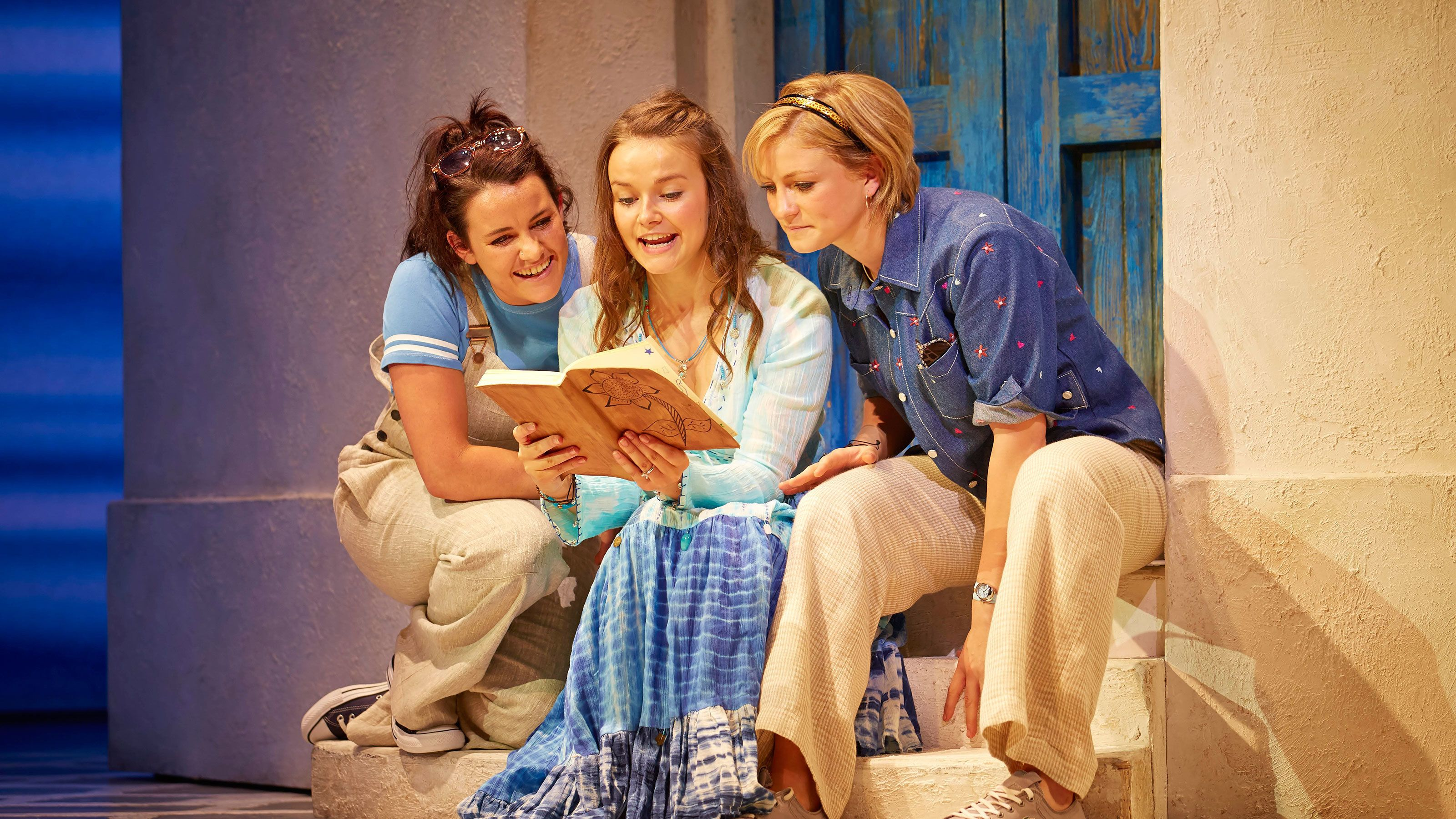 three actors reading a book on stage of Mama Mia in London