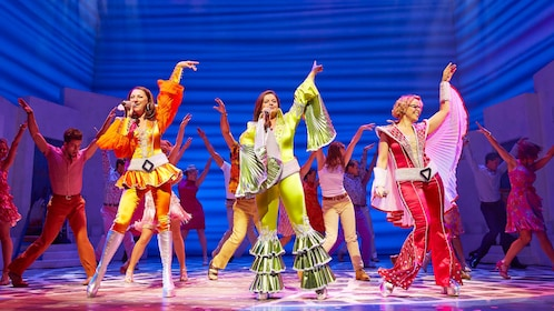 actors in colorful costumes dancing on stage at Mama Mia in London