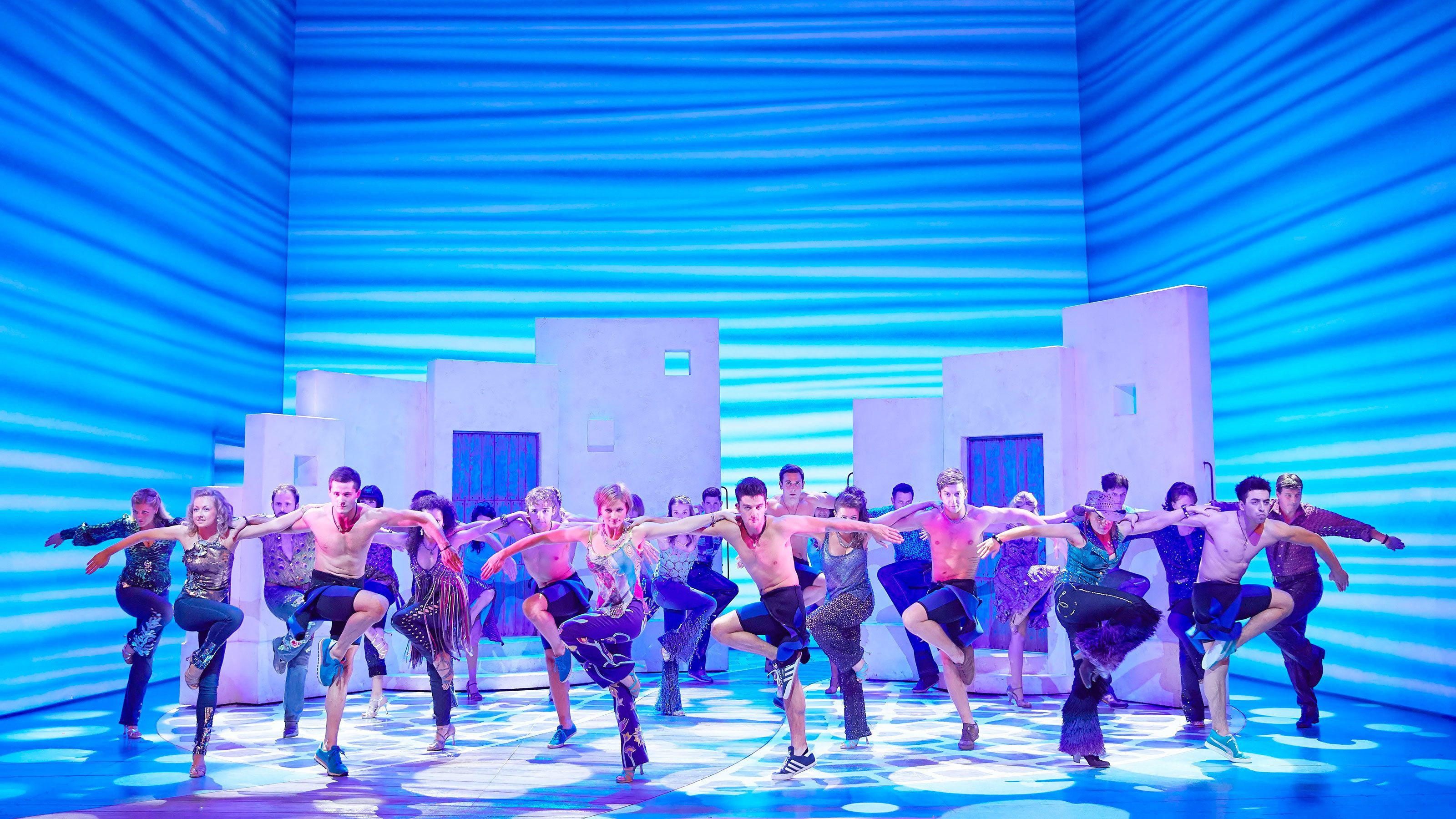 actors dancing on set of stage play of Mama Mia in London