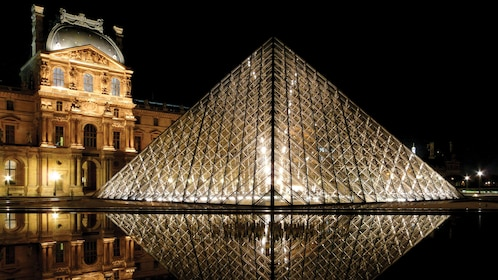 the louvre pyramid lit at night in Paris