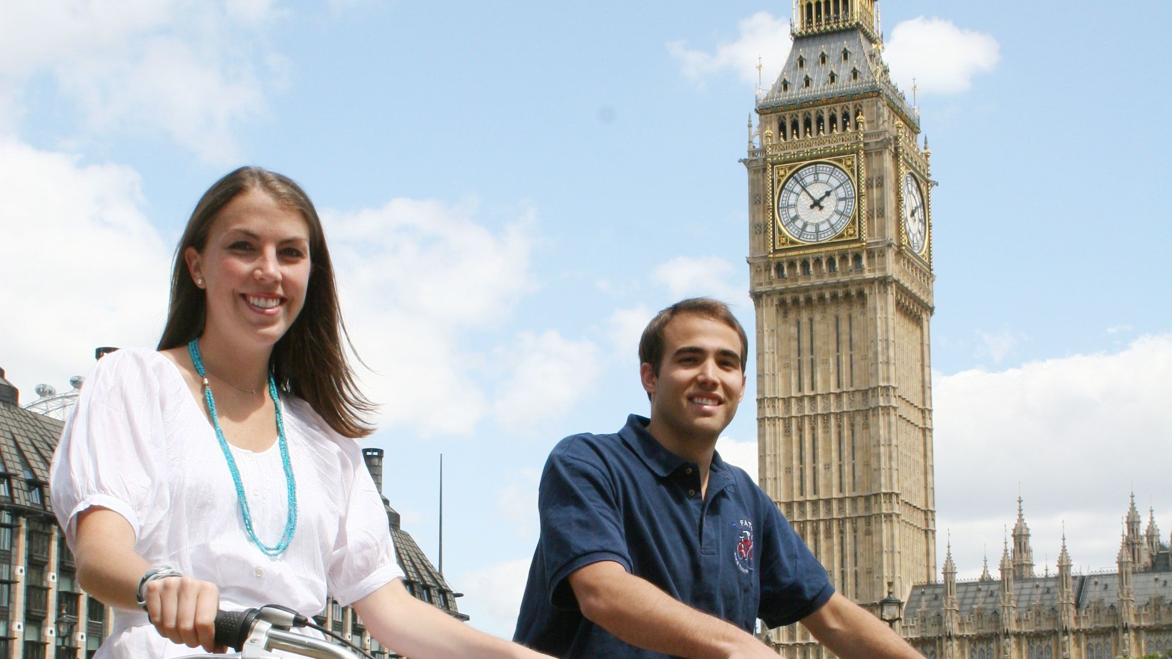 man and woman on bicycles next to Big Ben clock tower in London