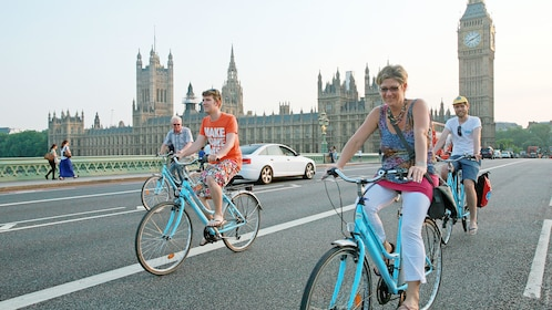 group of people riding cruiser bicycles past Parliament Building in London