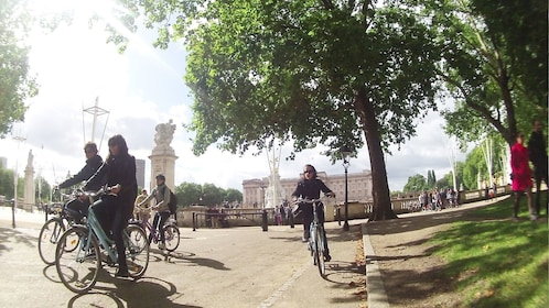 group of people riding cruiser bicycles pastLondon Flower garden