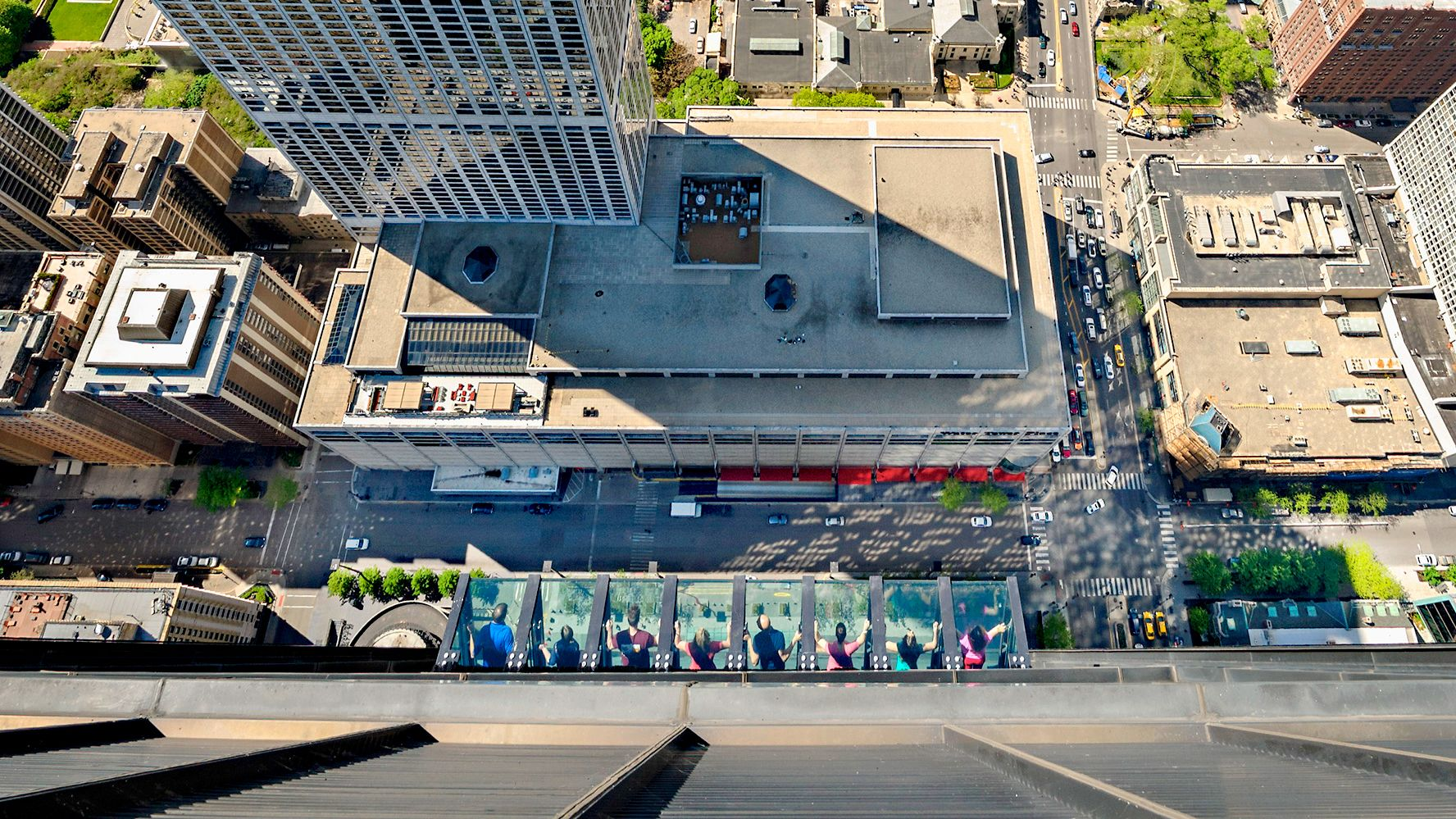 Aerial view of 8 people at the titled view in Willis Tower, Chicago