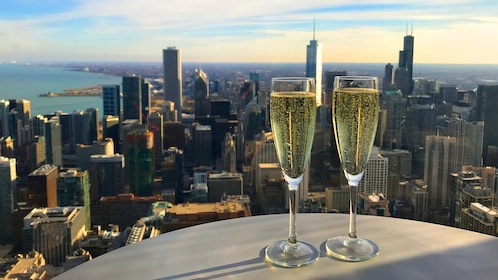 Two champagne flutes with the Chicago skyline as a background