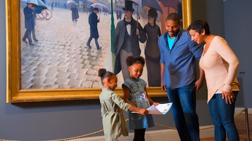 Family stands in front of a painting at the Art Institute of Chicago