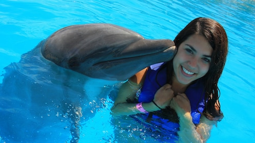 dolphin kissing woman on cheek in Los Cabos