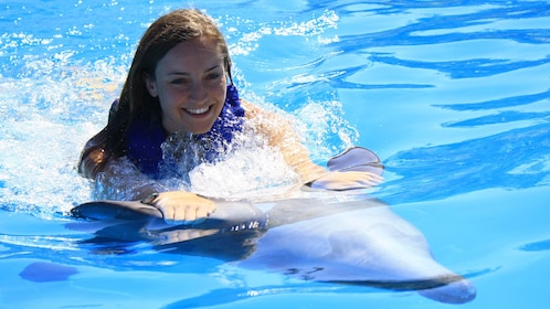 girl riding on dolphin in Los Cabos
