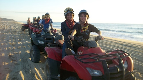 line of people riding ATV along a beach in Los Cabos