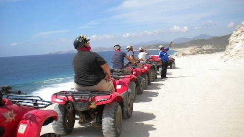 people driving many ATV's riding along shoreline in Los Cabos
