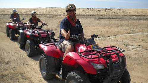 three people riding at ATV's on the beach in Los Cabos