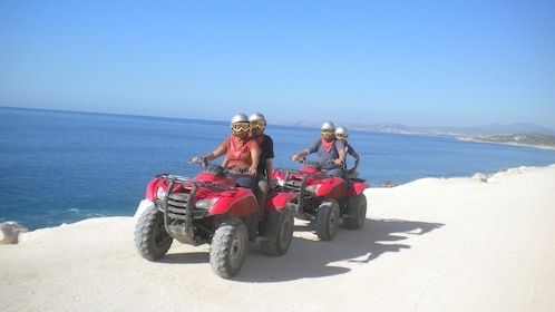 people driving two ATV's riding along shoreline in Los Cabos