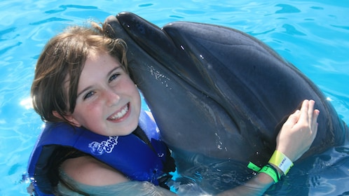 young girl hugging dolphin in Los Cabos