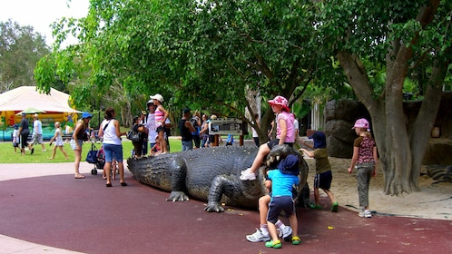 children sitting on a crocodile sculpture at the zoo in Australia