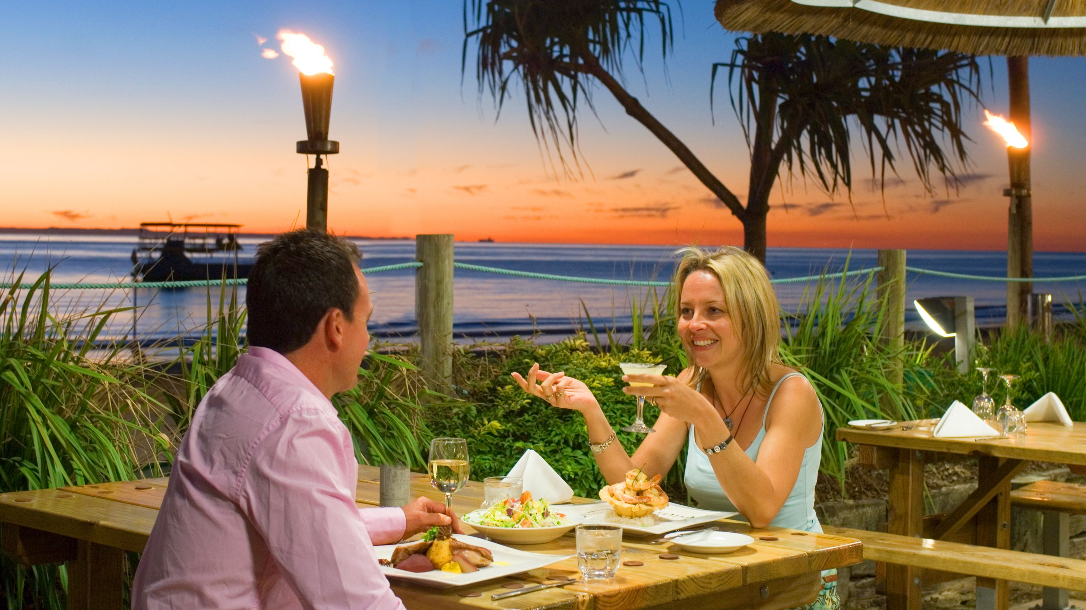 Two people eating dinner at an outdoor patio in Tangalooma Island
