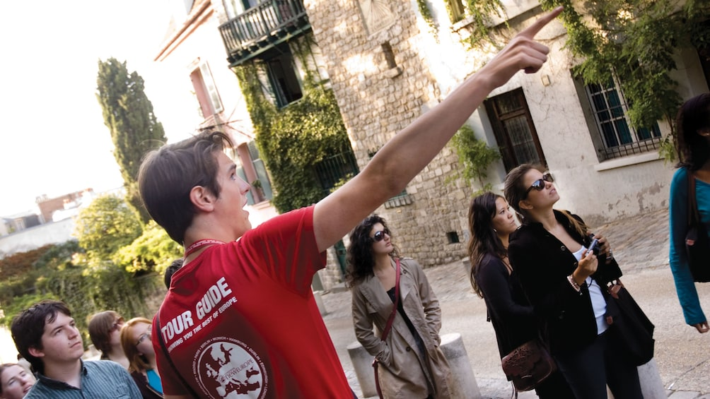 Show item 1 of 6. Tour guide pointing to a building in Paris.
