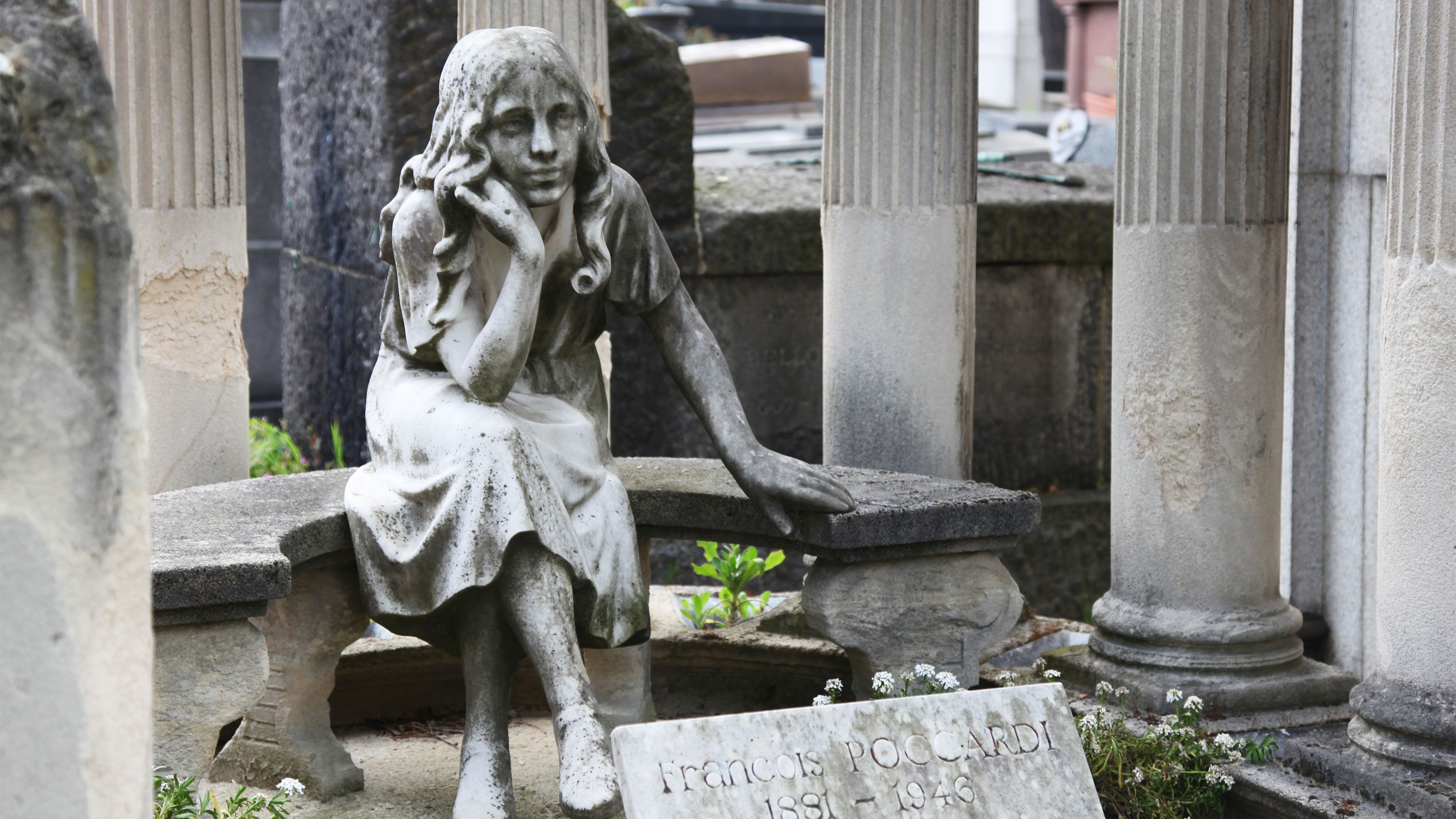 Statue of a young girl on a grave in Paris.