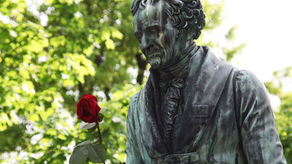 Statue of a man with a rose in a graveyard in Paris.