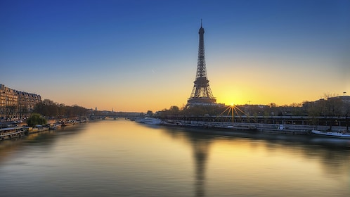 The Eiffel Tower overlooking the Seine river at sunset in Paris.