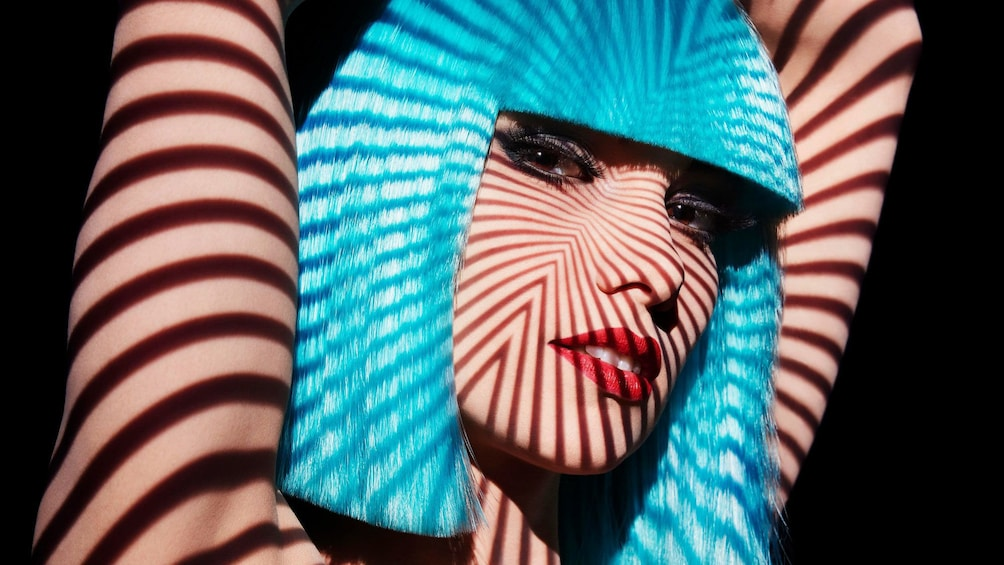 Cabaret performer in striped lighting during show  at the Crazy Horse in Paris