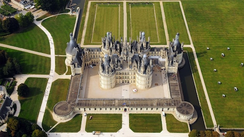 Aerial view of a French Chateau and surrounding countryside.