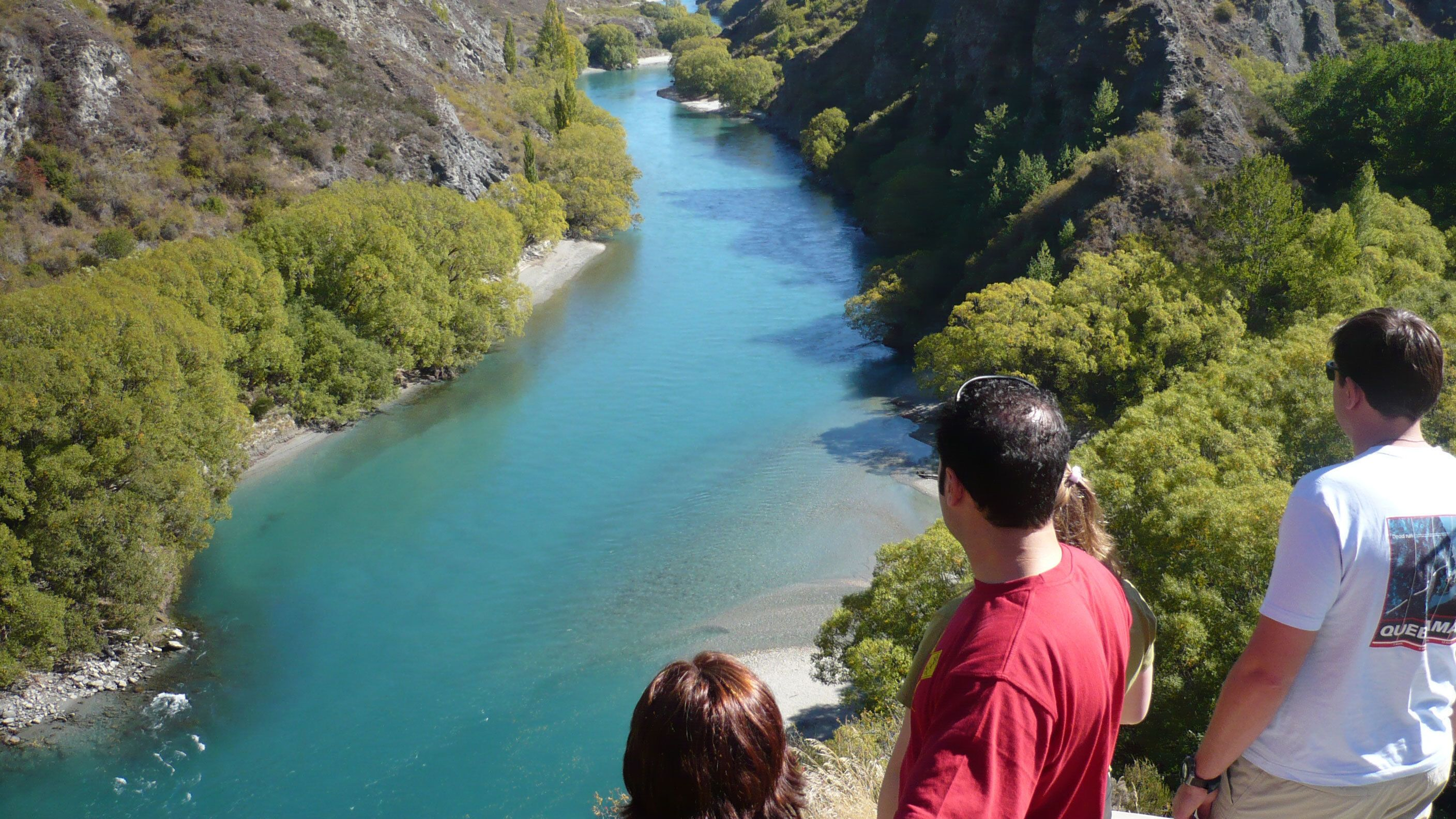 travelers looking down on a river from the top of a hill in New Zealand