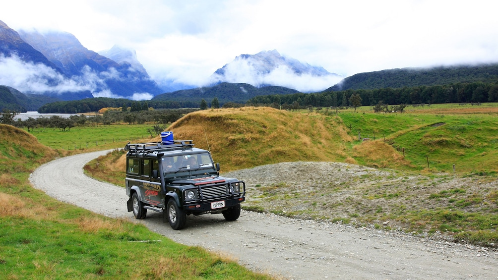 Show item 3 of 7. riding a safari vehicle on a gravel road in New Zealand