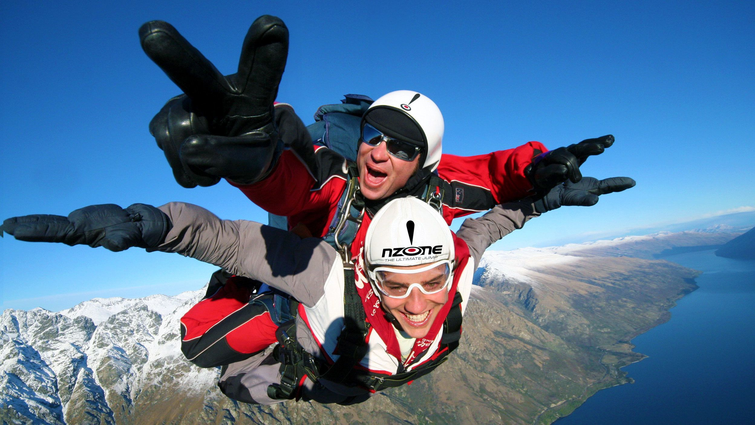 strapped skydiving instructor posing with diver in New Zealand